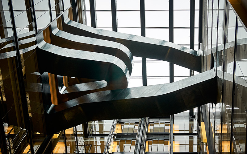 Staircase in blackened stainless steel with over-wax finish for Google, 6 Pancras Square, London, UK - Architects: AHMM - Main contractor: ISG - Staircase fabrication, installation and finishing: John Desmond Ltd - Structural engineers for John Desmond Ltd: AECOM - Showing view from below the stairs. Photography by Tim Soar