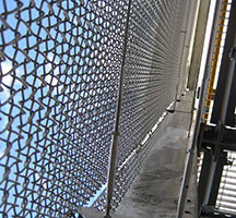 Chain link curtain wall running 100m length in Wood Lane tube station, London