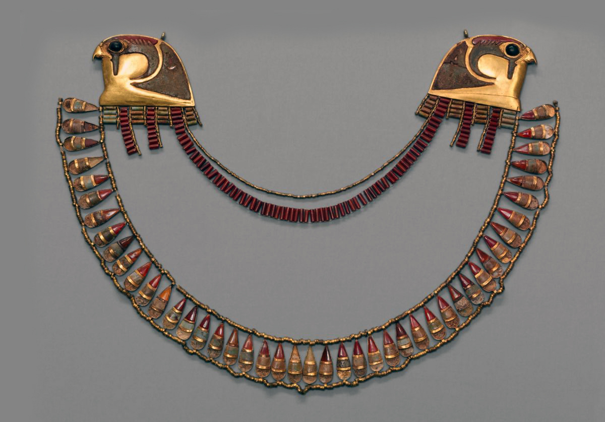 Broad gold collar made in the reign of Thutmose III ca 1479 – 1425 BC. Made from Gold, Carnelian, Obsidian and Glass. Displayed at the Metropolitan Museum, Fifth Avenue. The necklace was a gift from King Thutmose to one of his three wives as indicated by the inscription of his name on the back of one of the falcon heads.